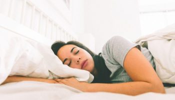 a-woman-sleeping-in-a-bright-white-bedroom_t20_Qalg7m